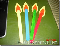 popsicle sticks painted to look like candles. small wooden craft pieces make the flame