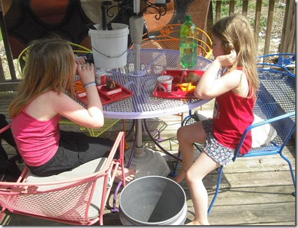 Girls eating lunch on side porch, on our rainbow patio set.