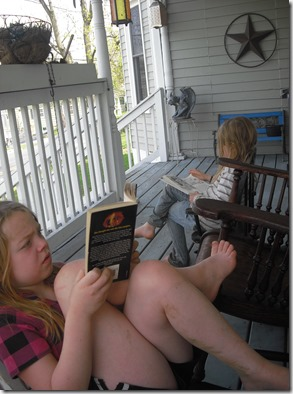 Girls reading books on the front porch after helping in the garden.