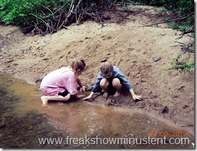 girls playing in the sand next to the stream